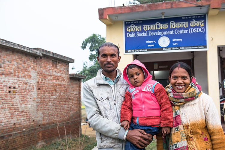Parshuram Harijan (left), 31 years old, son Sakcham, 4 years old and wife Mayadevi (right) pose for a picture in front of the Dalit Social Development Center. Parshuram works here as a social mobilizer. CARE USA representatives have come to the area to view the progress of the Tipping Point Program, meant to combat child marriage in the districts of Kapilbastu and Rupandehi of Nepal near the Indian border.